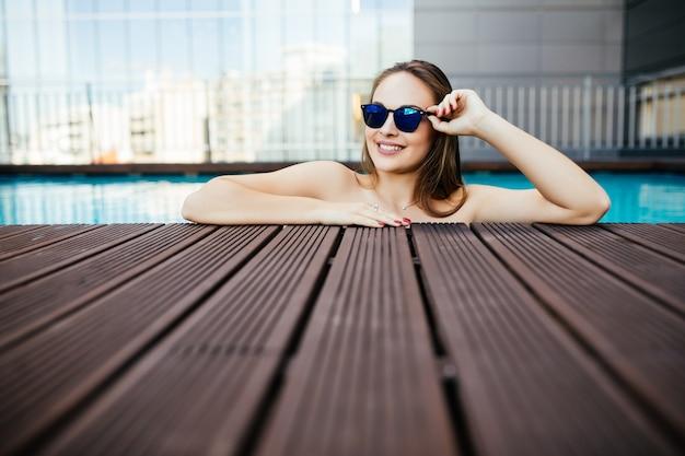 Retrato de uma linda mulher em óculos de sol, posando à beira da piscina, dia de verão, ao ar livre