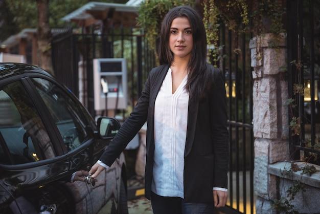 Retrato de uma linda mulher em pé perto do carro