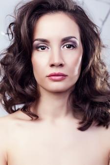 Retrato de uma linda mulher em um fundo cinza em foto de estúdio. profissional maquiagem e penteado. elegância e romance