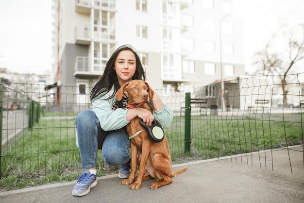 Retrato de uma linda mulher em um vestido casual sentada com um cachorro na cidade