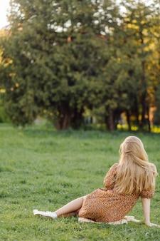 Retrato de uma linda mulher em um vestido preguiçoso na grama verde no campo, a natureza nas férias do dia de verão