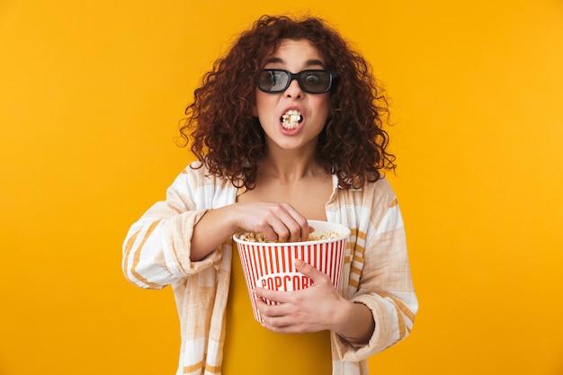 Retrato de uma linda mulher encaracolada chocou fofo posando isolado na parede amarela usando óculos comer filme de relógio de pipoca.