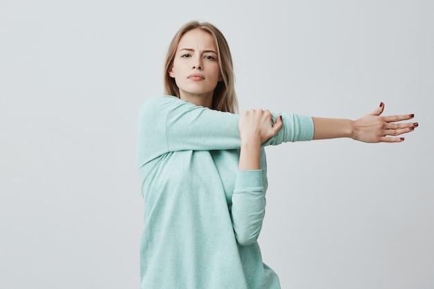 Retrato de uma linda mulher europeia com cabelos longos loiros, vestindo blusa azul casual, esticando o braço dela, fazendo exercícios, se preocupa com sua saúde. conceito de fitness, saúde e beleza.