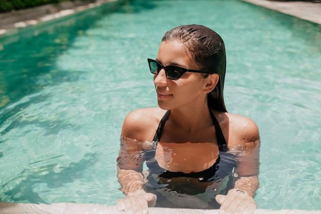 Retrato de uma linda mulher fabulosa usando óculos escuros elegantes, posando na piscina