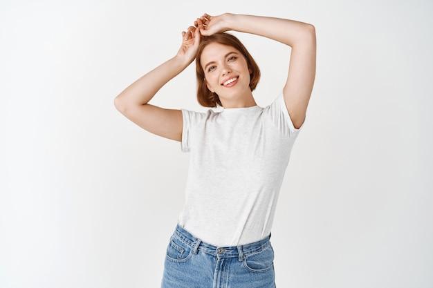 Retrato de uma linda mulher feliz com maquiagem de luz natural, descansando as mãos na cabeça e sorrindo, em pé de jeans e camiseta na parede branca