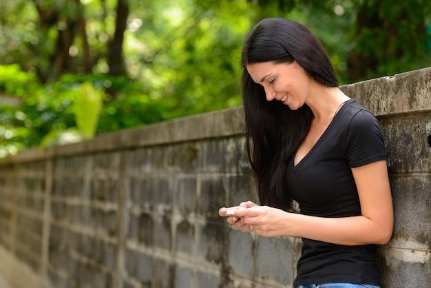 Retrato de uma linda mulher feliz usando o telefone ao ar livre