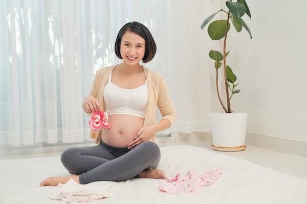 Retrato de uma linda mulher grávida com as roupas do seu futuro bebê