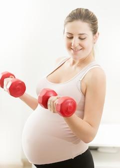 Retrato de uma linda mulher grávida levantando halteres