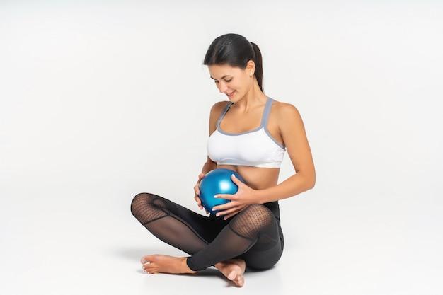 Retrato de uma linda mulher grávida sentada no chão com bola de fitness isolada
