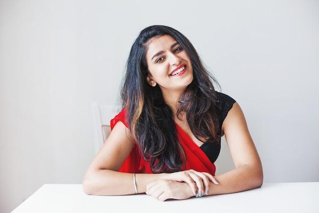 Retrato de uma linda mulher indiana em saree sentado à mesa