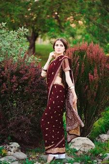 Retrato de uma linda mulher indiana. modelo de jovem hindu com tatoo mehndi e jóias kundan. saree de traje indiano tradicional.