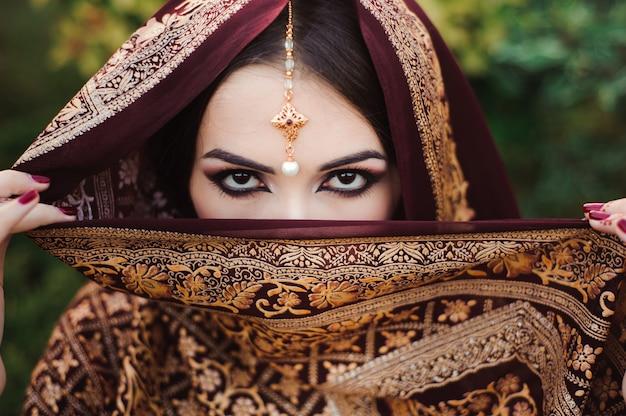 Retrato de uma linda mulher indiana. modelo de jovem hindu com tatoo mehndi e jóias kundan.