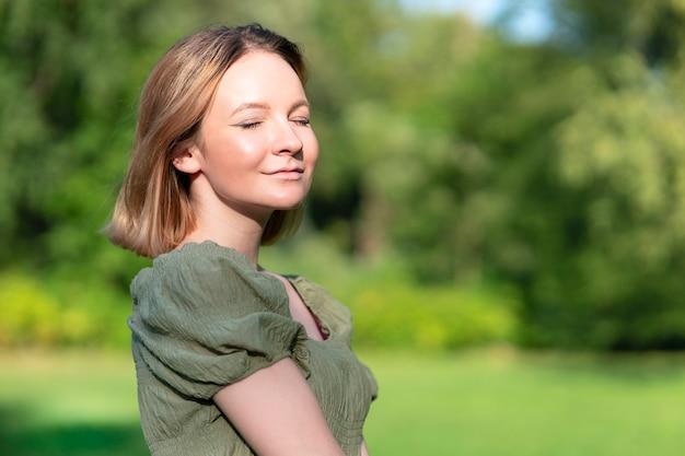 Retrato de uma linda mulher jovem e atraente menina bonita está caminhando, desfrutando de respirar ar fresco e limpo na floresta verde de verão ou parque com os olhos fechados, tomando banho de sol em um dia ensolarado. fundo natural