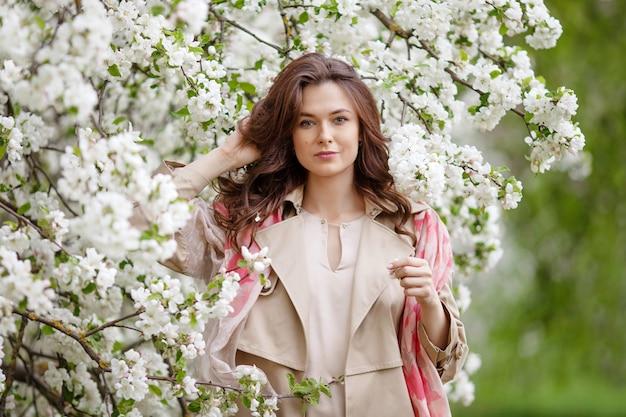 Retrato de uma linda mulher jovem morena sorridente no jardim de macieira flor na primavera. aproveite a natureza. menina saudável ao ar livre. conceito de primavera. linda garota no pomar