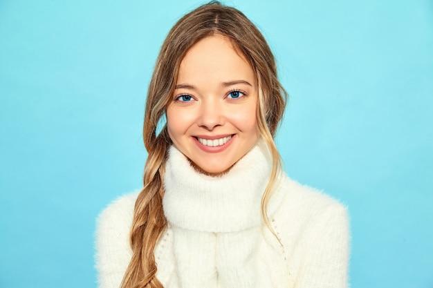 Retrato de uma linda mulher linda loira sorridente. mulher que está na camisola branca à moda, na parede azul. conceito de inverno