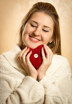 Retrato de uma linda mulher loira abraçando um coração de malha vermelha