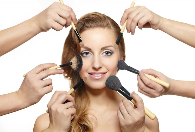 Retrato de uma linda mulher loira com cabelos longos e pincéis de maquiagem perto do rosto atraente