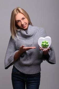 Retrato de uma linda mulher loira com caixa de presente em forma de coração
