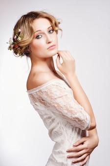Retrato de uma linda mulher loira com flores no cabelo dela.