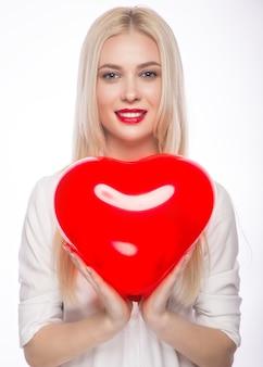 Retrato de uma linda mulher loira com maquiagem brilhante e coração vermelho na mão