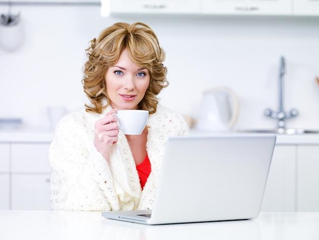 Retrato de uma linda mulher loira com uma xícara de café e laptop sentado na cozinha