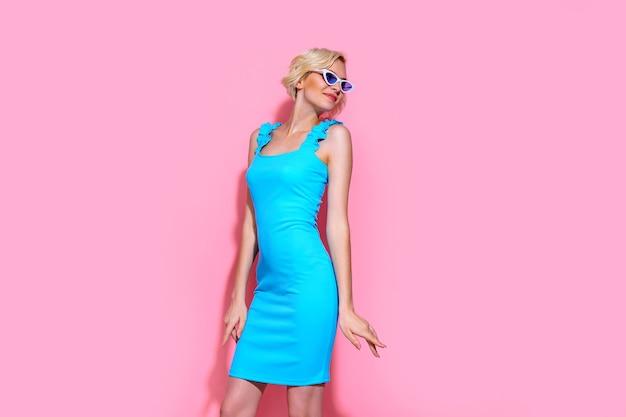 Retrato de uma linda mulher loira com vestido azul e óculos de sol, posando no fundo rosa do estúdio