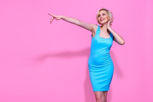 Retrato de uma linda mulher loira com vestido azul, posando no fundo rosa do estúdio, apontando o dedo para.