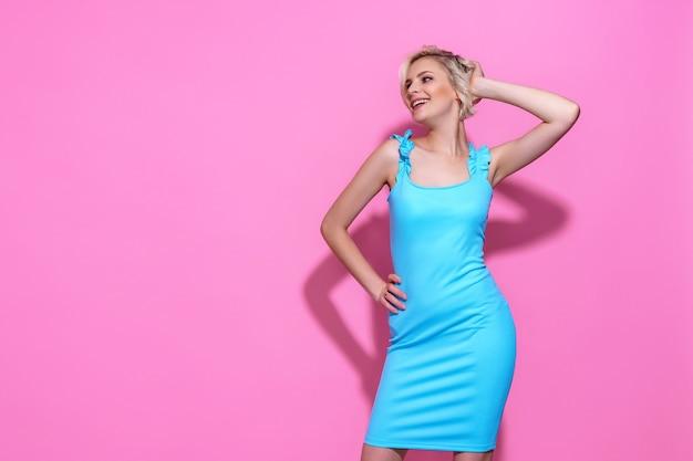 Retrato de uma linda mulher loira com vestido azul, posando no fundo rosa do estúdio