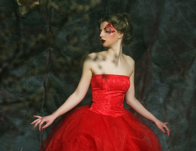 Retrato de uma linda mulher loira com vestido vermelho. penteado e maquiagem criativos. filmado em uma casa de fantasia.