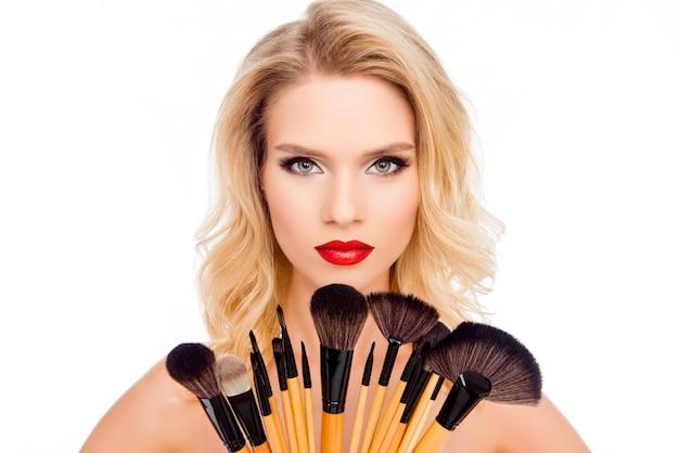 Retrato de uma linda mulher loira de luxo segurando pincéis para maquiagem