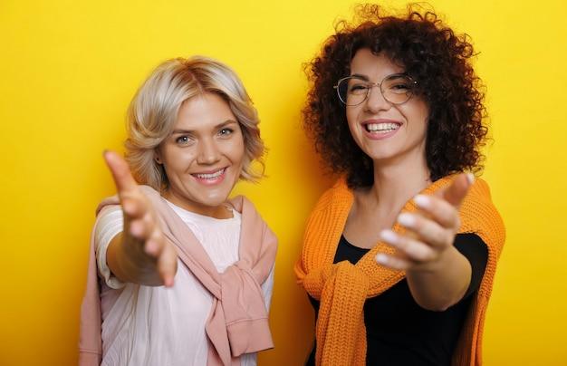 Retrato de uma linda mulher loira e uma encantadora mulher encaracolada olhando para a câmera rindo enquanto segura sua mão para dar as boas-vindas aos jovens contra a parede amarela.