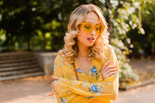 Retrato de uma linda mulher loira elegante com blusa amarela usando óculos escuros, colorido tendência da moda de verão, dia de sol brilhante