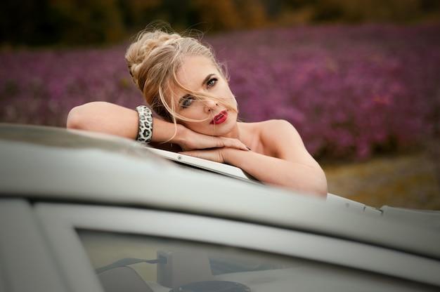 Retrato de uma linda mulher loira, estilo francês, com carro perto de campo de lavanda