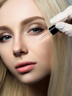 Retrato de uma linda mulher loira no salão de beleza. cosmetologista aplicando gotas de beleza