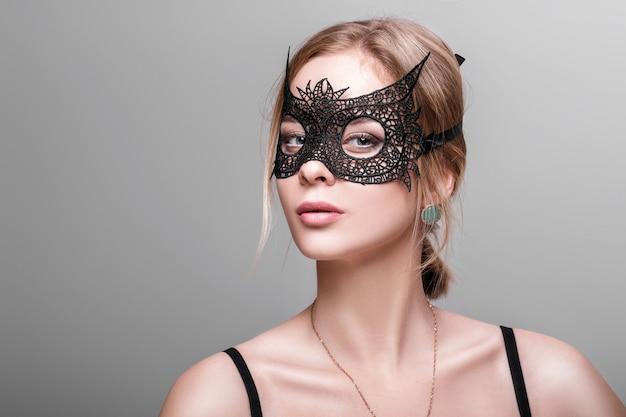 Retrato de uma linda mulher loira sensual com olhos verdes em máscara de renda preta sobre um fundo escuro. máscara veneziana
