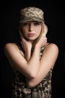 Retrato de uma linda mulher loira soldados em traje militar em fundo preto. tristeza e desespero
