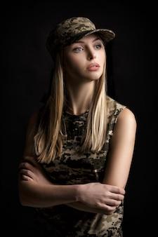 Retrato de uma linda mulher loira, soldados em traje militar em fundo preto