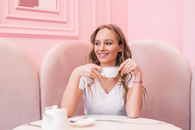 Retrato de uma linda mulher madura, bebendo uma xícara de chá na cafeteria. mulher feliz em um café bebendo café.