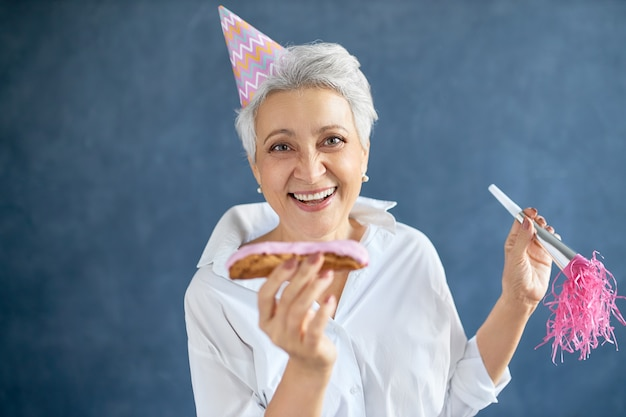 Retrato de uma linda mulher madura caucasiana com corte de cabelo curto e grisalho usando chapéu cônico