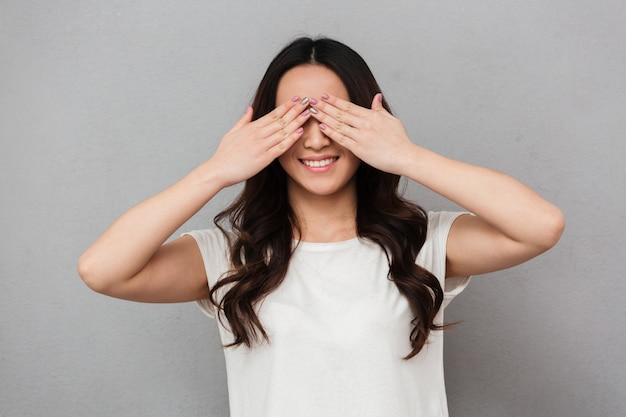 Retrato de uma linda mulher morena com cabelos longos, sorrindo e cobrindo o rosto com as palmas das mãos, isolado sobre a parede cinza