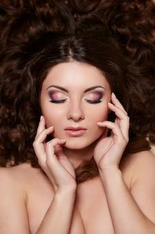 Retrato de uma linda mulher morena, com longos cabelos cacheados e maquiagem brilhante