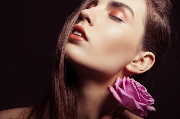 Retrato de uma linda mulher morena com rosa