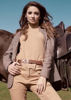 Retrato de uma linda mulher morena com uma elegante jaqueta xadrez marrom posando com um cavalo na paisagem do campo