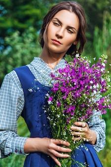 Retrato de uma linda mulher morena com vestido azul no campo