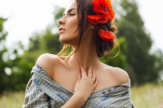 Retrato de uma linda mulher morena com vestido de flores vermelhas no cabelo no campo