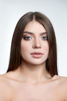 Retrato de uma linda mulher morena de olhos verdes com maquiagem na