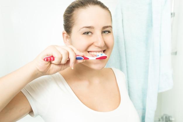 Retrato de uma linda mulher morena escovando os dentes