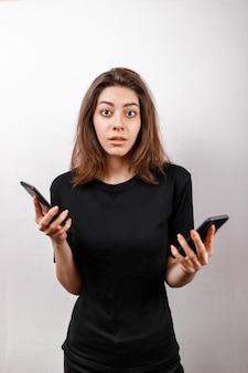Retrato de uma linda mulher morena europeia sorridente em uma camiseta preta, mostrando dois telefones celulares para seleção de vendas