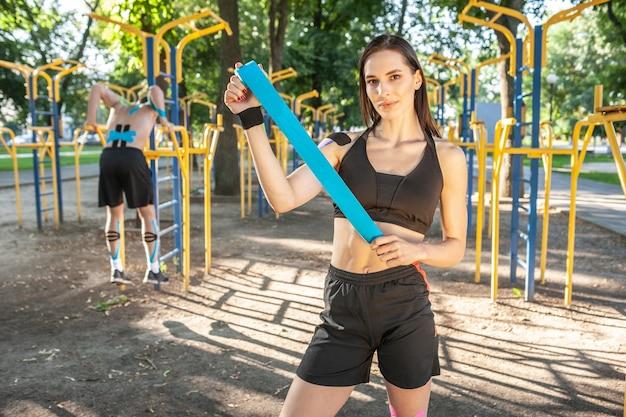 Retrato de uma linda mulher morena musculosa, olhando para a câmera. jovem atleta sorridente posando com fita azul kinesio nas mãos, homem treinando no fundo.