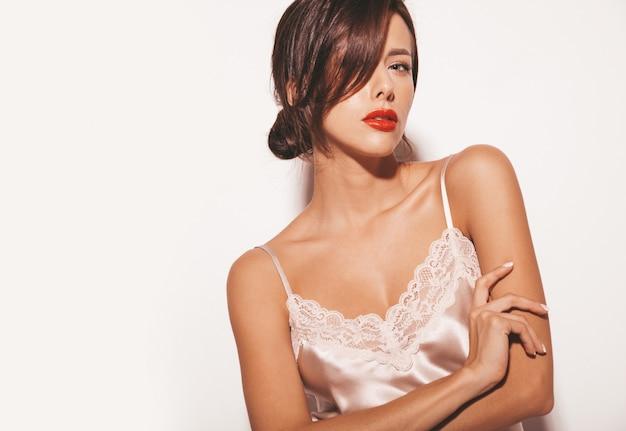 Retrato de uma linda mulher morena sensual. garota com roupas clássicas bege elegantes e calças largas. modelo isolado no branco